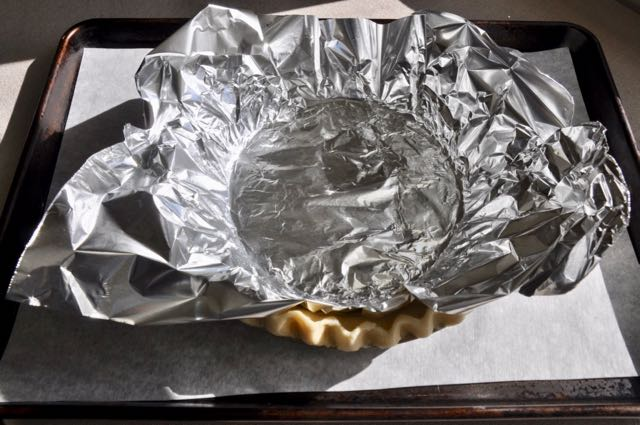 Prebaking a pie shell with foil and beans